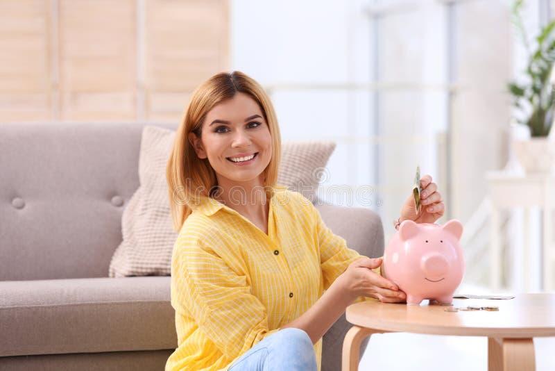 Женщина с копилкой и деньгами стоковые изображения