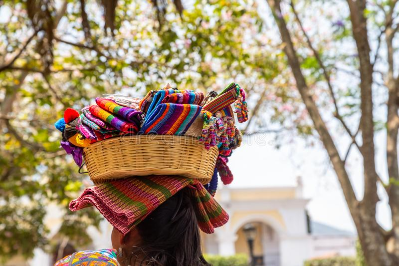 Женщина с корзиной с соевенирами на голове в городе Антигуа в Гватемале стоковое фото rf