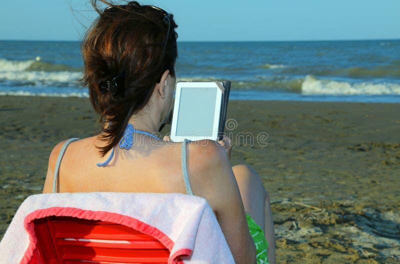 Женщина с коричневыми волосами читает ebook на пляже стоковая фотография