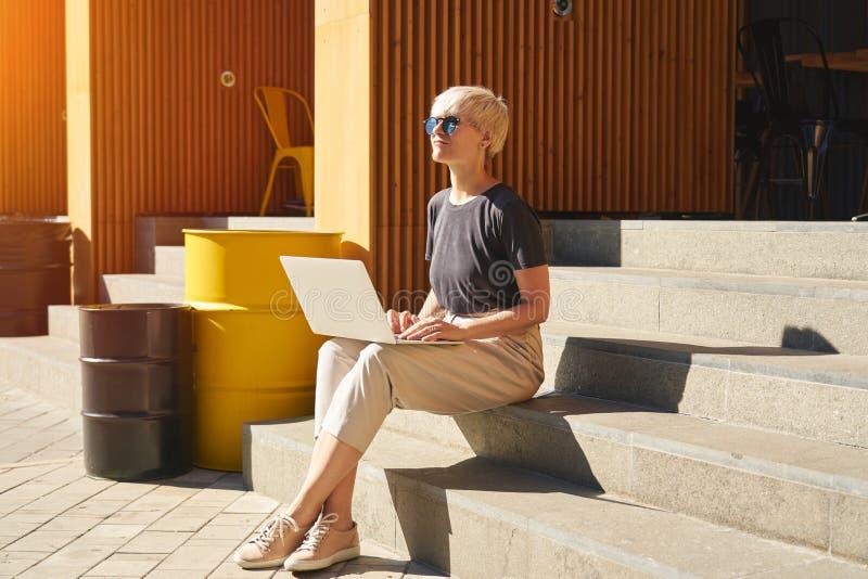 Женщина с короткими волосами, работающая на ноутбуке, посмотрите на небо, в солнцезащитных очках Сидя на лестнице, солнечный день стоковые фотографии rf