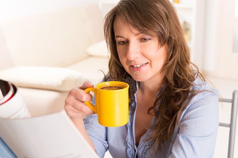Женщина с кофейной чашкой и газетой стоковая фотография rf