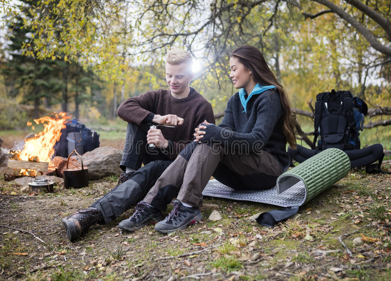 Женщина с кофе человека меля во время располагаться лагерем в лесе стоковые изображения