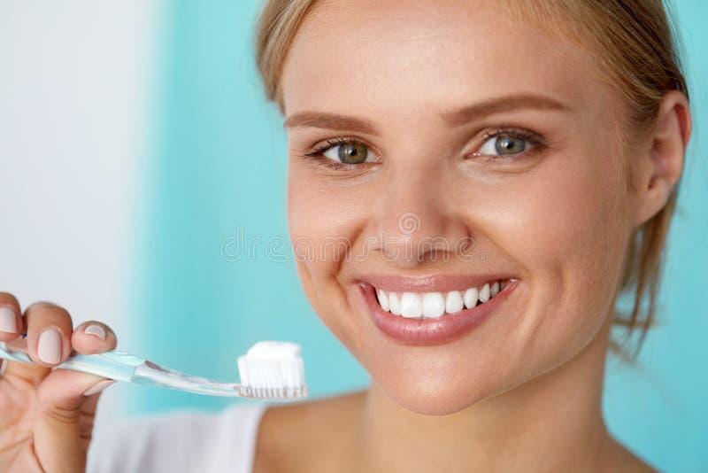 Женщина с красивой улыбкой, здоровые белые зубы с зубной щеткой стоковые изображения rf