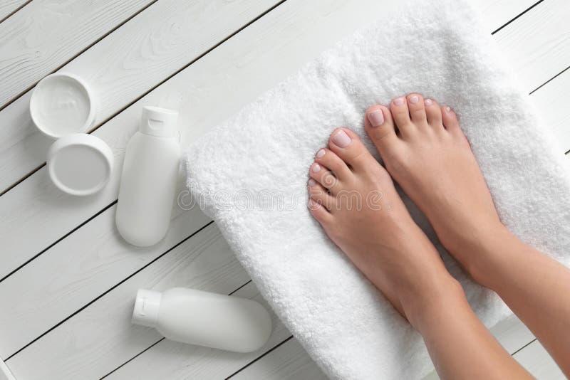 Женщина с красивыми ногами, полотенцем и косметическими продуктами на белом деревянном поле r стоковая фотография rf