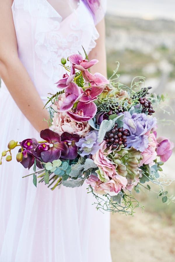 Женщина с красивым букетом цветков в ее руках стоит на горе в лучах захода солнца рассвета Красивое белое длинное стоковая фотография