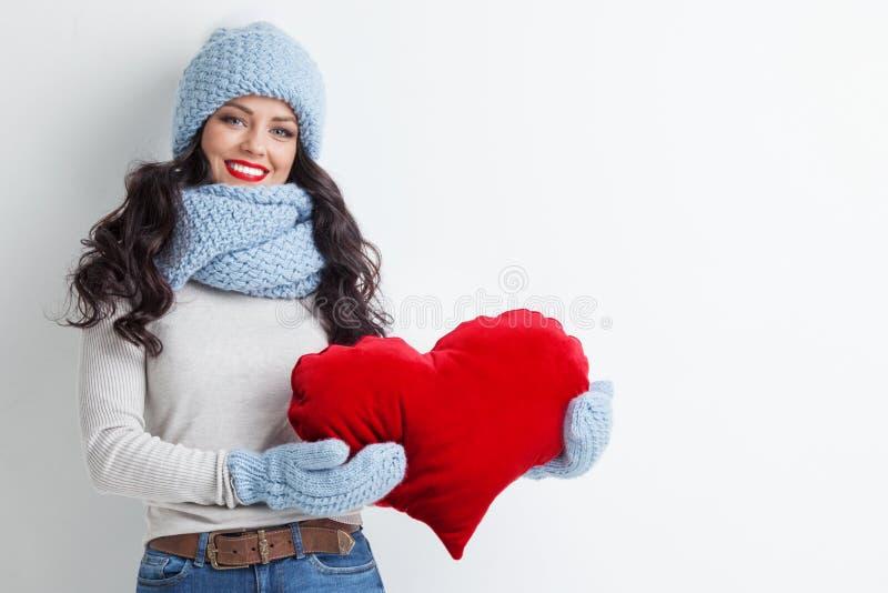 Женщина с красной подушкой формы сердца стоковое изображение