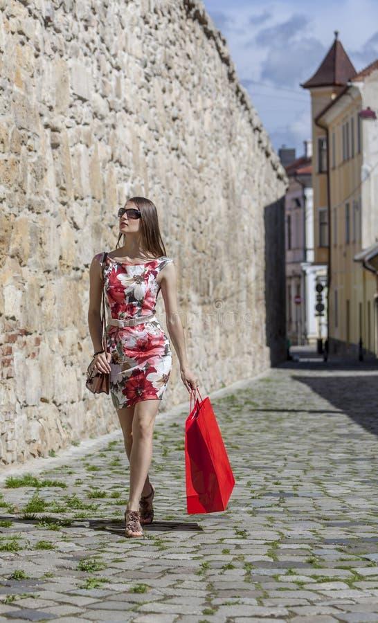 Женщина с красной хозяйственной сумкой в городе стоковая фотография
