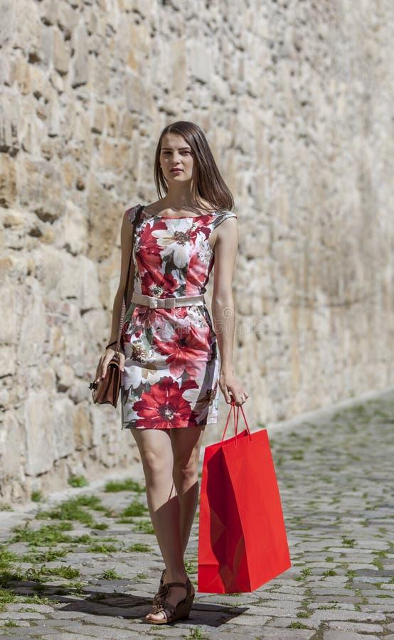 Женщина с красной хозяйственной сумкой в городе стоковые изображения