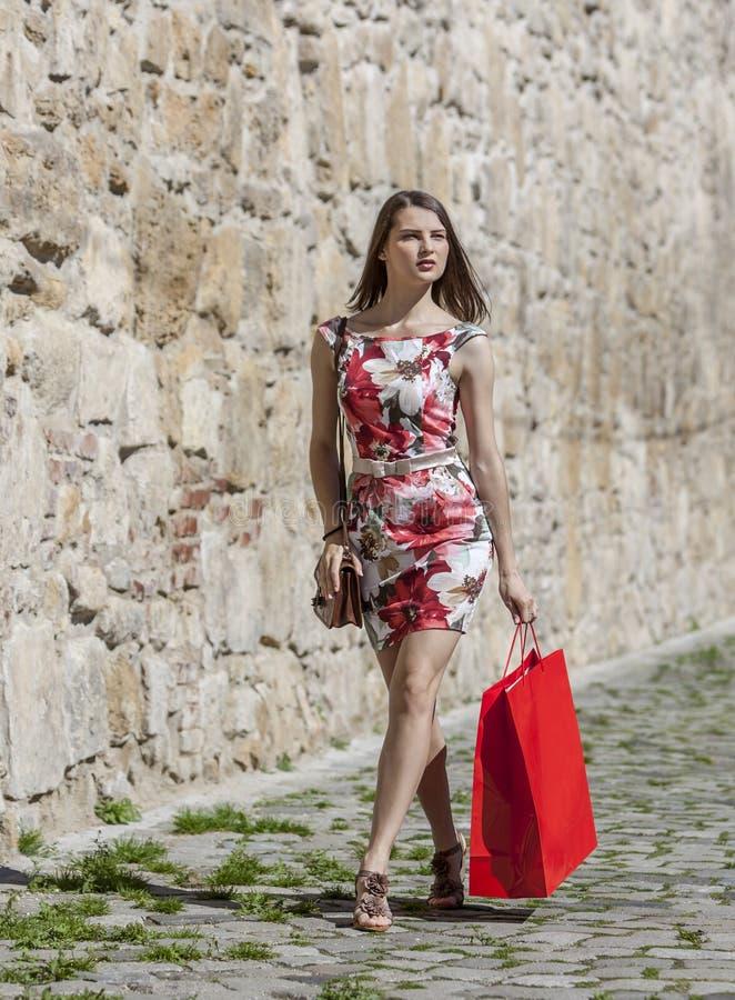 Женщина с красной хозяйственной сумкой в городе стоковые фото