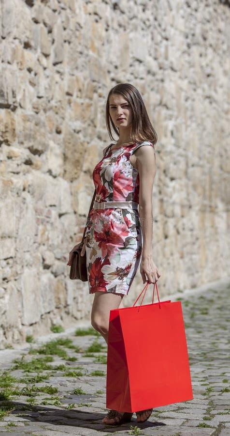 Женщина с красной хозяйственной сумкой в городе стоковые изображения rf