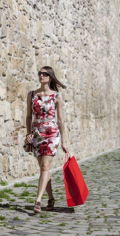 Женщина с красной хозяйственной сумкой в городе стоковая фотография rf