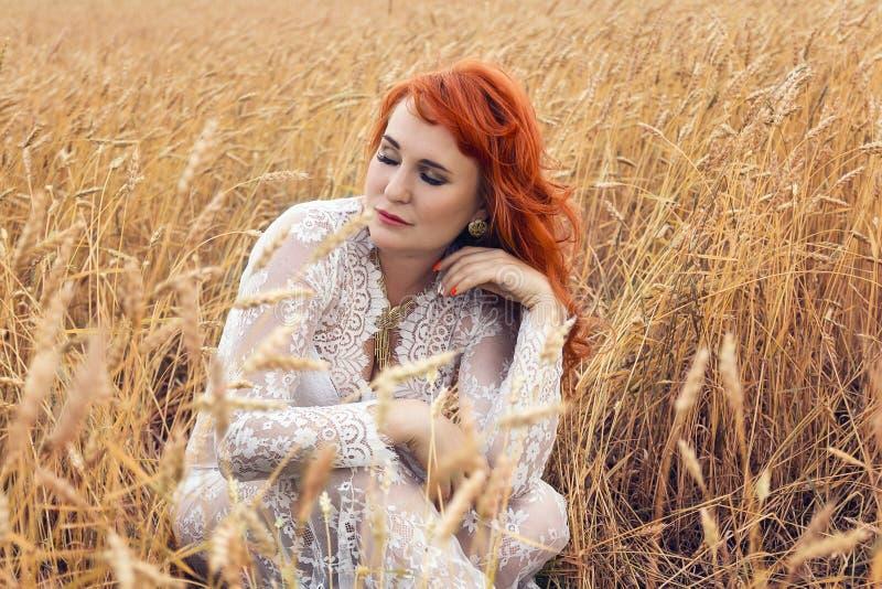 Женщина с красными волосами в пшеничном поле стоковое изображение