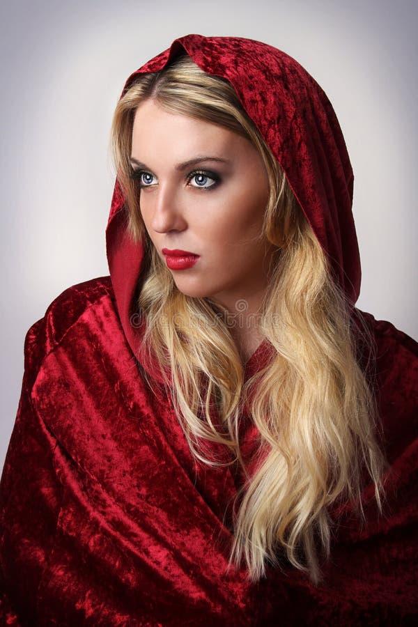 Женщина с красными клобуком и плащой-накидк стоковая фотография rf