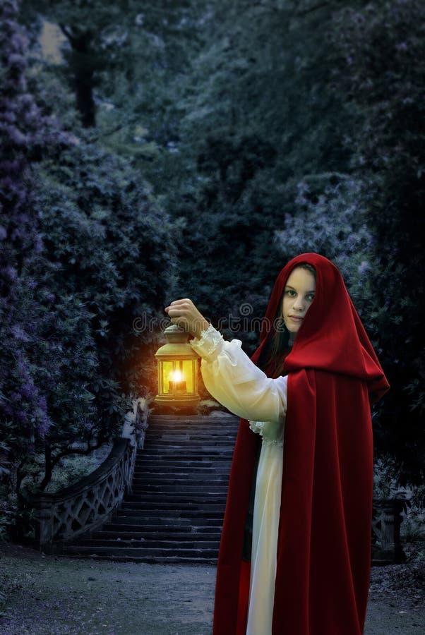 Женщина с красными накидкой и фонариком стоковое фото rf