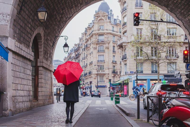 Женщина с красным зонтиком идя на улицу Парижа стоковая фотография