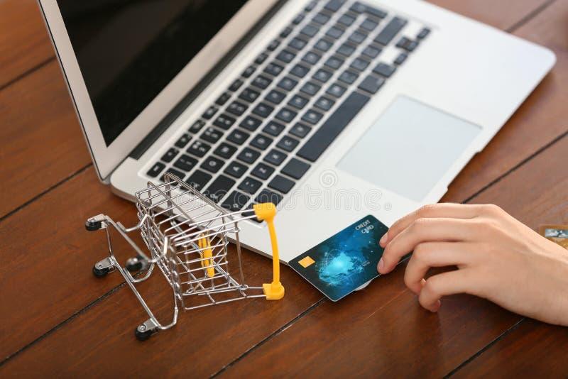 Женщина с кредитной карточкой, небольшой тележкой используя ноутбук на деревянном столе, крупном плане E стоковое фото rf