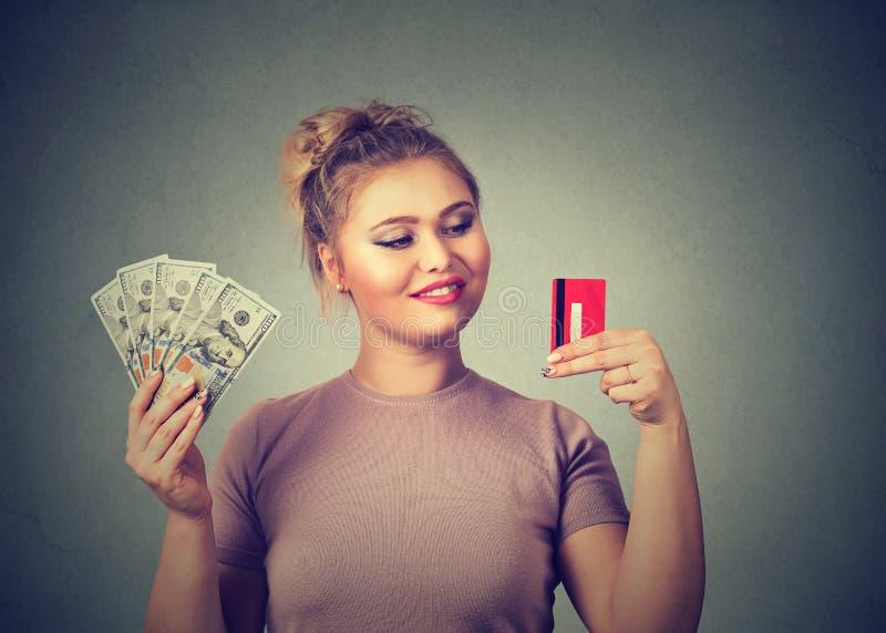 Женщина с кредитной карточкой и доллар получают счастливое наличными с выбором банка стоковые фото