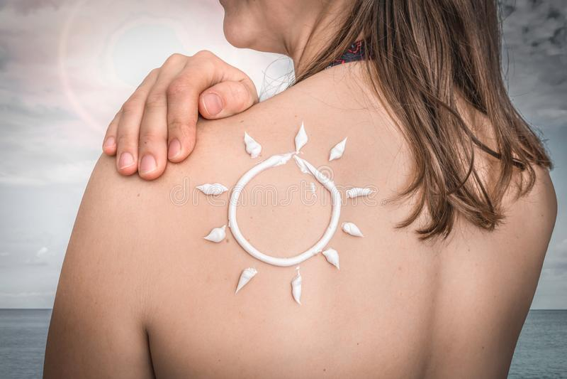 Женщина с лосьоном suntan на ее плече в форме солнца стоковые изображения
