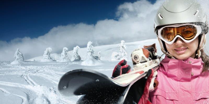 Женщина с лыжами на снежном наклоне стоковое фото rf