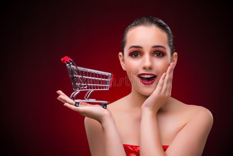 Женщина с магазинной тележкаой против красной предпосылки стоковое изображение rf