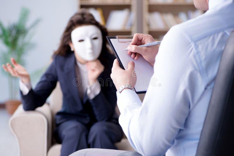 Женщина с маской во время посещения психолога стоковые изображения rf