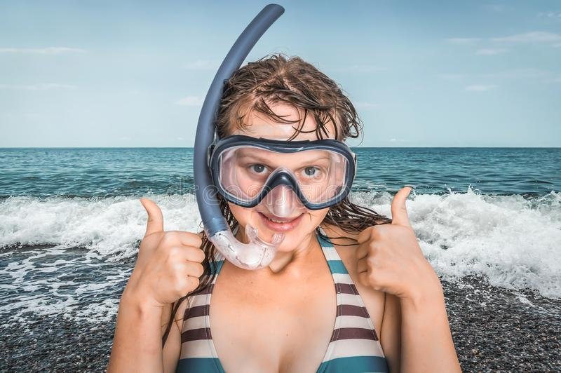 Женщина с маской для ныряя стоек около моря стоковая фотография