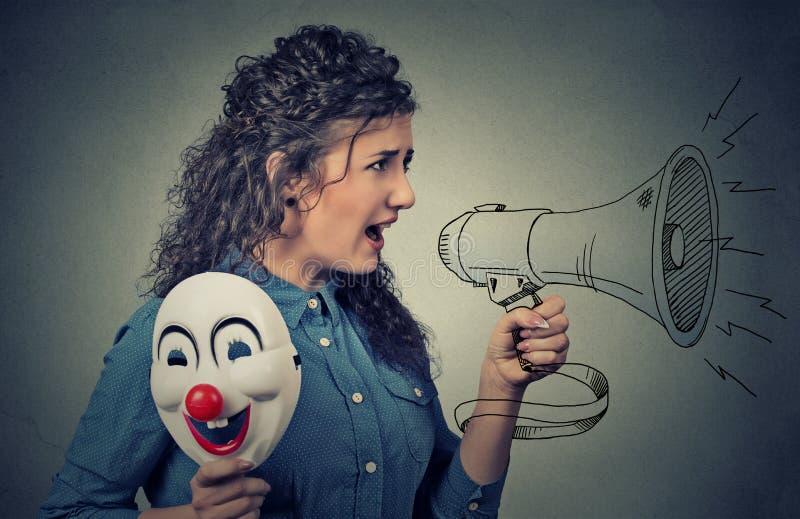 Женщина с маской мегафона и клоуна стоковые фото