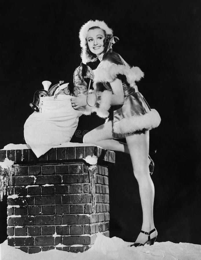 Женщина с мешком gifs рождества и снежная печная труба (все показанные люди более длинные живущие и никакое имущество не существу стоковые фотографии rf