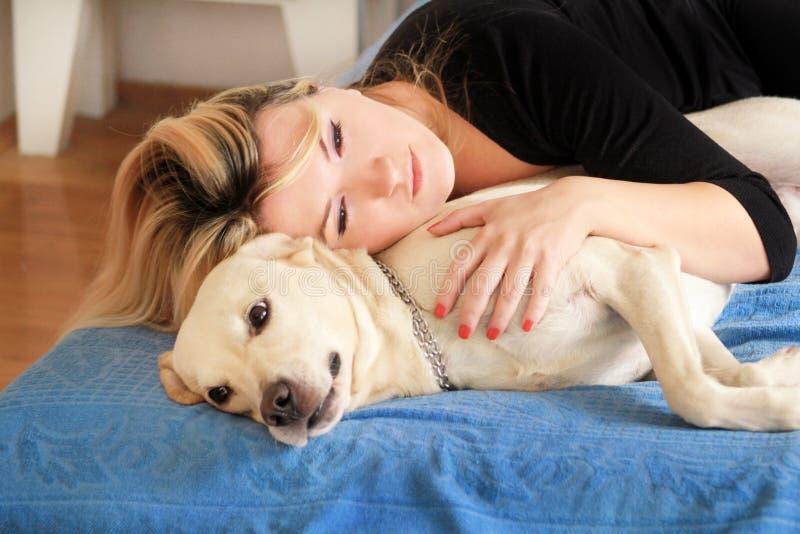 Женщина с милыми собаками дома Красивая девушка отдыхая и спать с ее собакой в кровати в спальне Предприниматель и собака спать в стоковое изображение rf