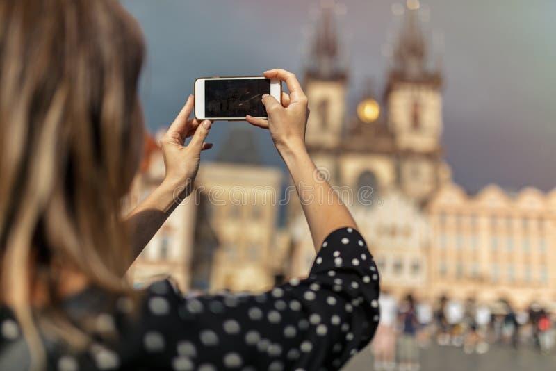 Женщина с мобильным телефоном сделала снимок старого города в Праге стоковое фото