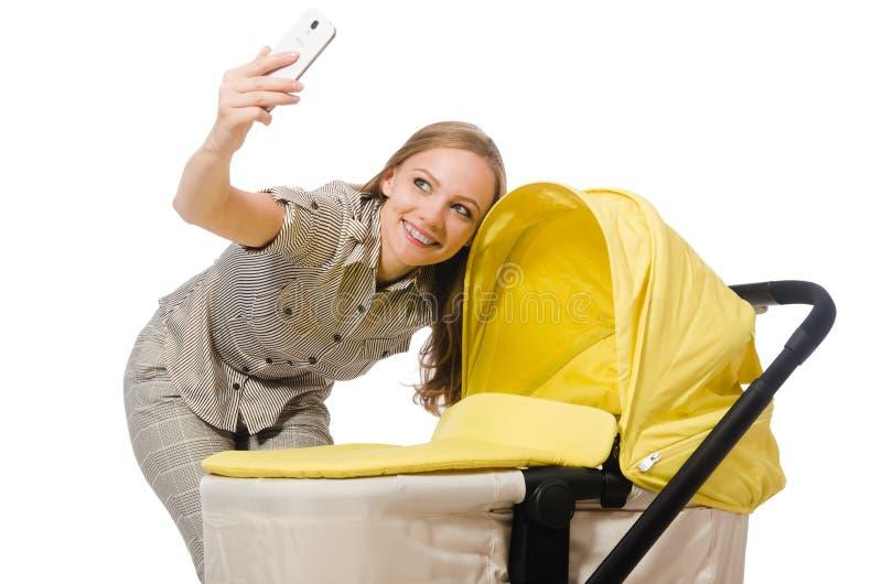Женщина с младенцем и pram изолированный на белизне стоковые фотографии rf