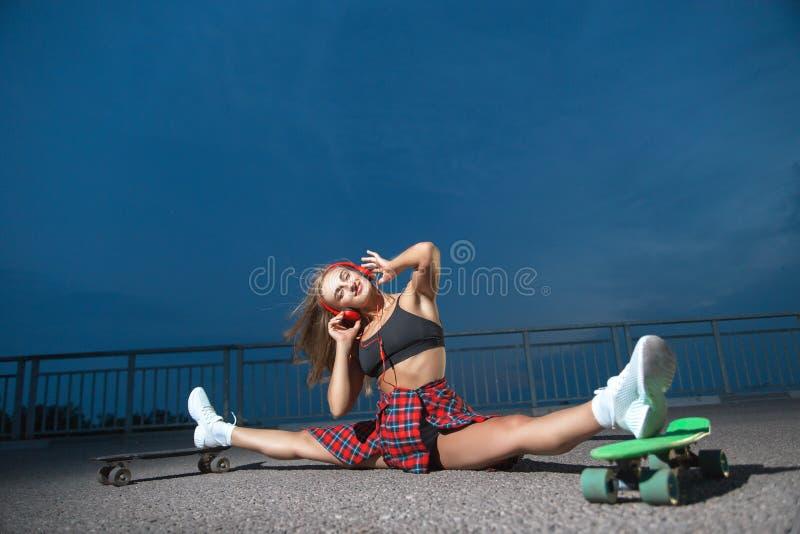 Женщина с наушниками и скейтбордами стоковые фотографии rf