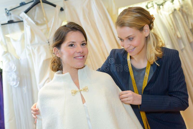 Женщина с невестой выбирает белую накидку на магазине свадьбы стоковые изображения rf