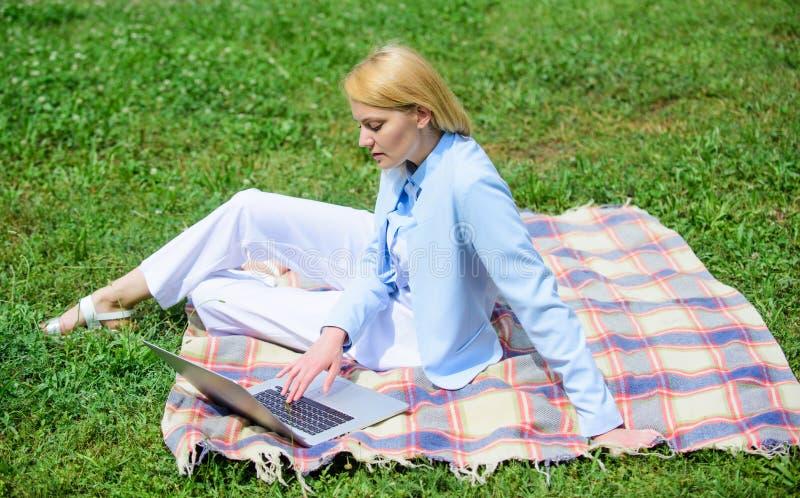 Женщина с ноутбуком или тетрадь сидят на луге травы зеленого цвета половика Шаги, который нужно начать работать не по найму дело  стоковые изображения