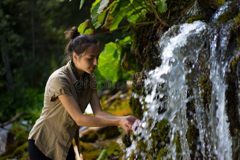 Женщина с обеими руками на водопаде стоковое фото
