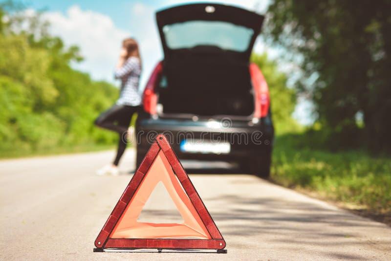 Женщина сломанная вниз на проселочной дороге вызывая для помощи тонизированное изображение стоковое фото