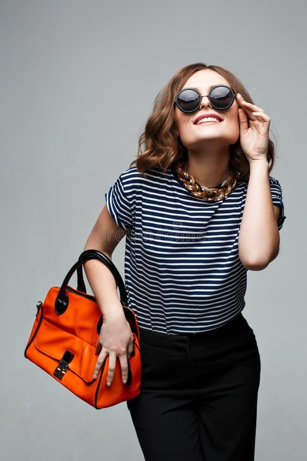 Женщина с оранжевой сумкой в студии солнечные очки, стоковое фото