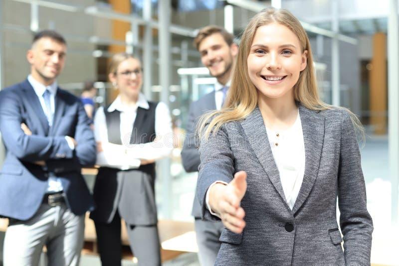Женщина с открытой рукой готовой для рукопожатия в офисе стоковые фотографии rf