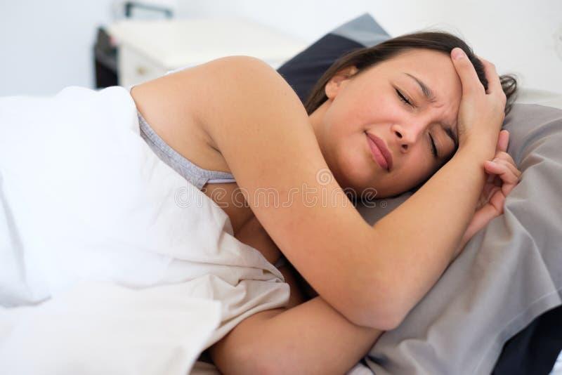 Женщина с очень сильной головной болью в кровати стоковая фотография rf