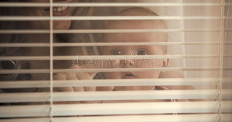 Женщина с пальцем пункта ребенка на шторках окна стоковые изображения rf