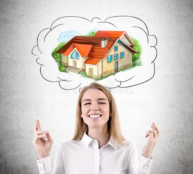Женщина с пересеченными пальцами мечтает о доме стоковое изображение rf