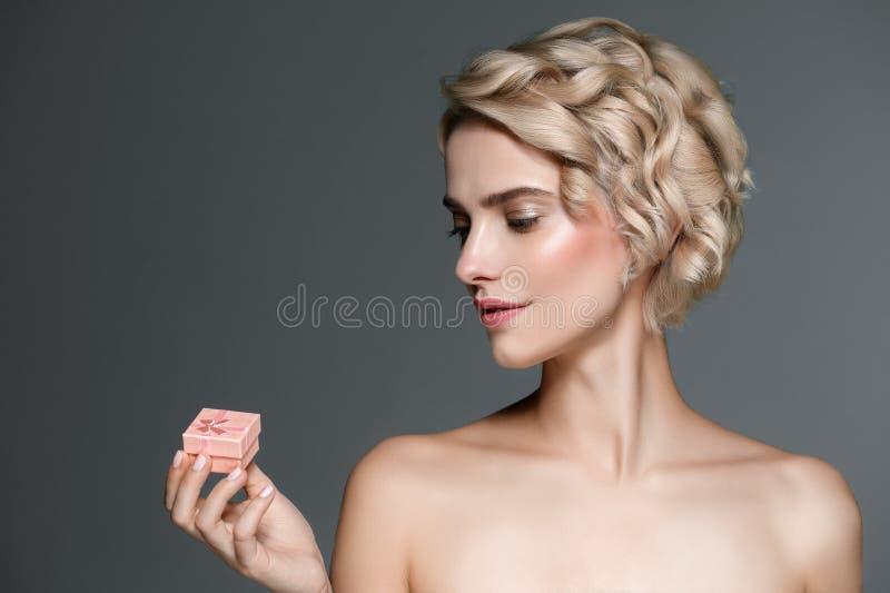 Женщина с подарочной коробкой в руках над серой предпосылкой стоковые изображения rf