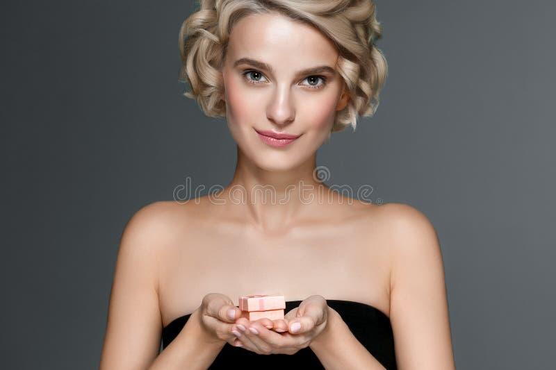 Женщина с подарочной коробкой в руках над серой предпосылкой стоковое фото