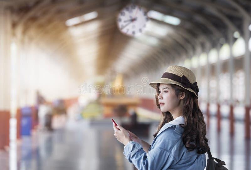 Женщина с положением рюкзака и smartphone использования на железной дороге стоковое изображение rf