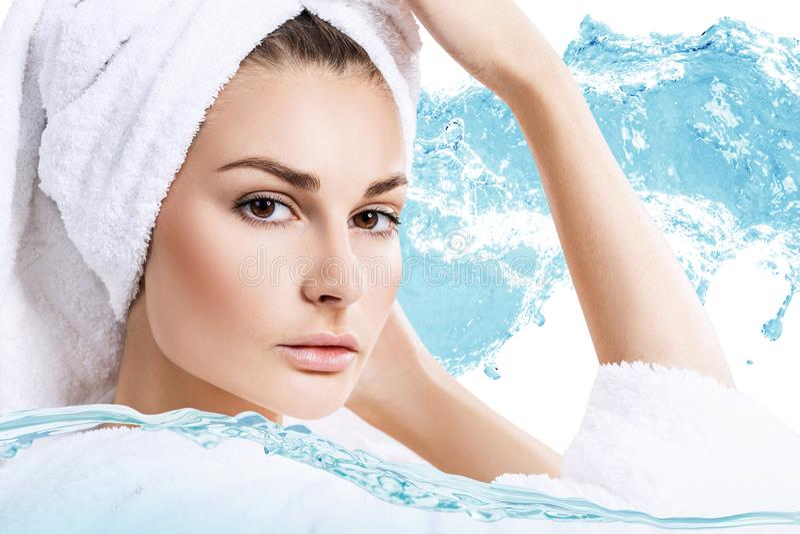 Женщина с полотенцем ванны на голове в воде брызгает стоковые фото