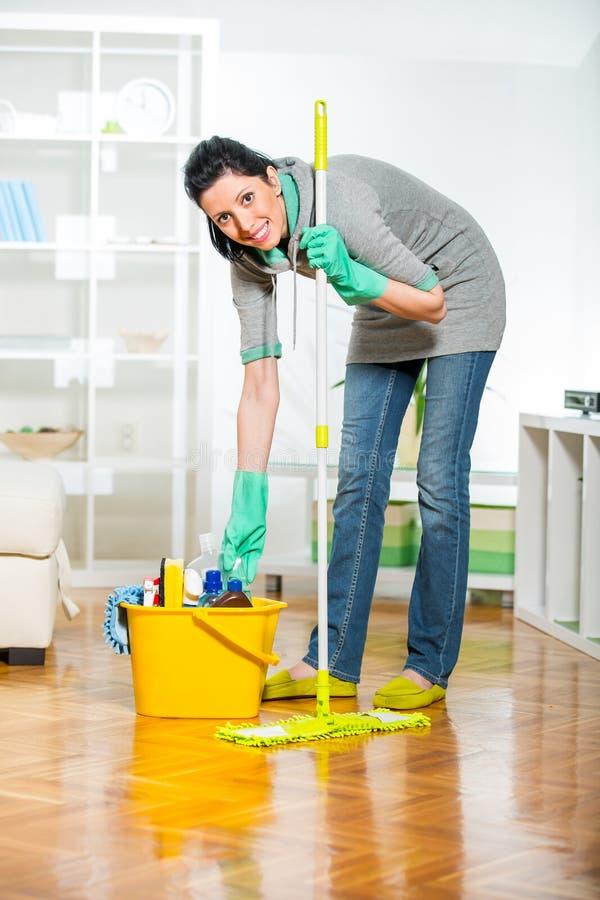 Женщина с поставками чистки в живущей комнате стоковые фотографии rf