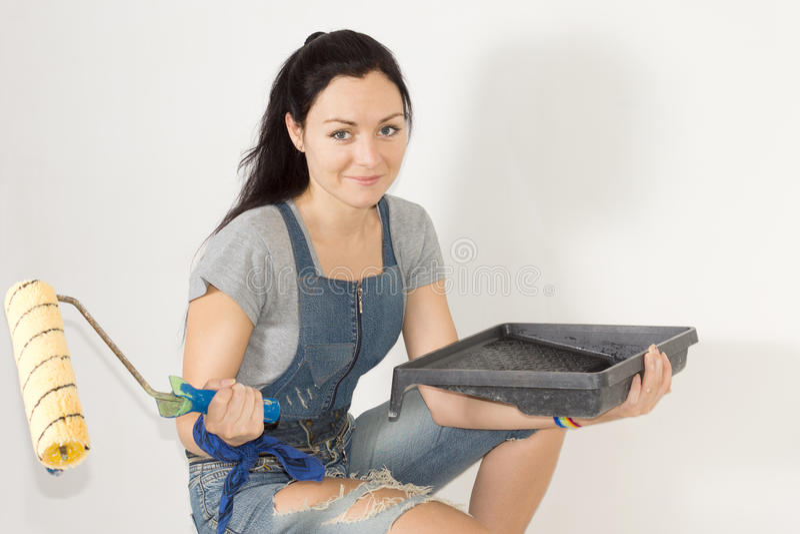 Женщина с подносом и роликом краски стоковые фото