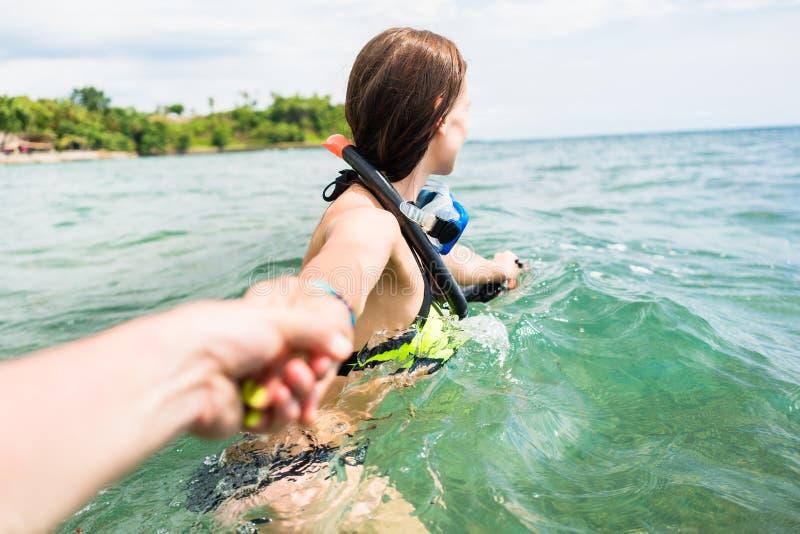 Женщина с подныриванием гуглит волоча партнера к морю стоковое изображение rf