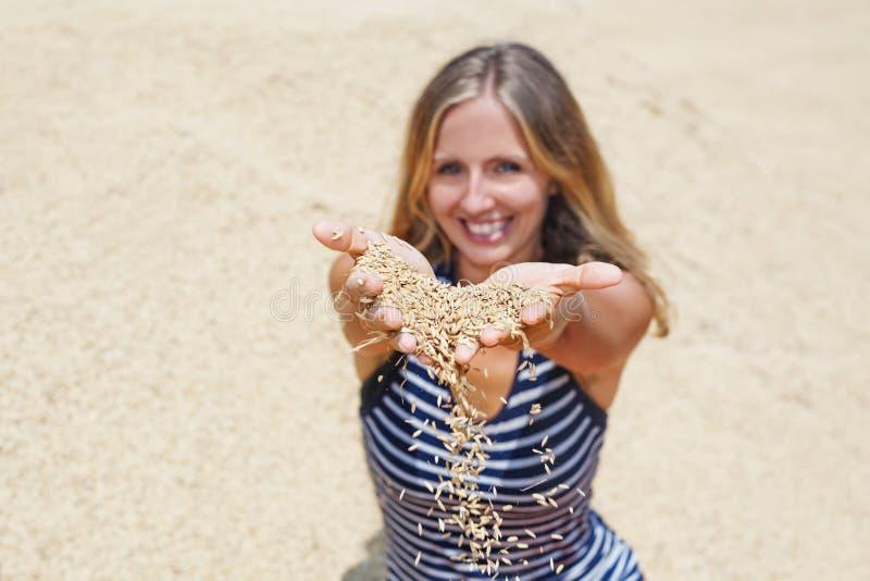 Женщина с пригорошней сырцовых зерен риса в руках стоковая фотография rf
