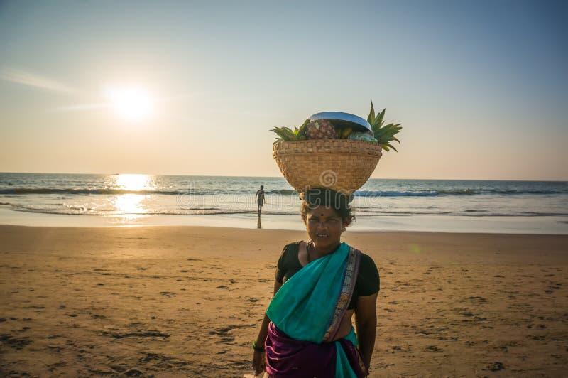 Женщина с плетеной корзиной на его головном продавая плодоовощ на пляже, Индии, Gokarna стоковые изображения